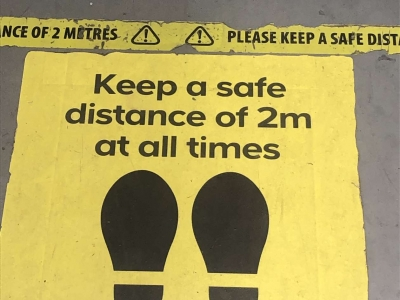Photo: Pavement with notice to Keep safe distance of 2 meters